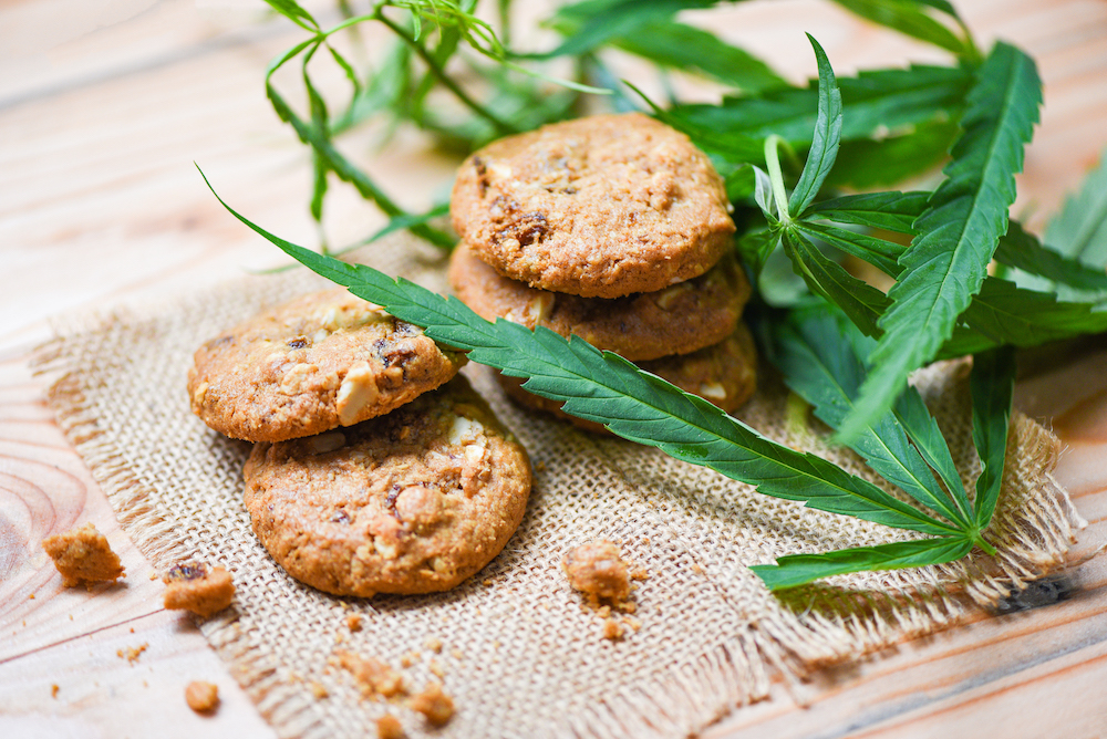 The benefits of cooking with Cannabis at Pure Life Wellness in Baltimore | Cookies with cannabis leaf marijuana herb on sack wooden background - cannabis food snack for health